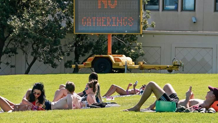 Unbekümmert «sünnele»: In Australien immer noch möglich - trotz der warnenden Tafel im Hintergrund.