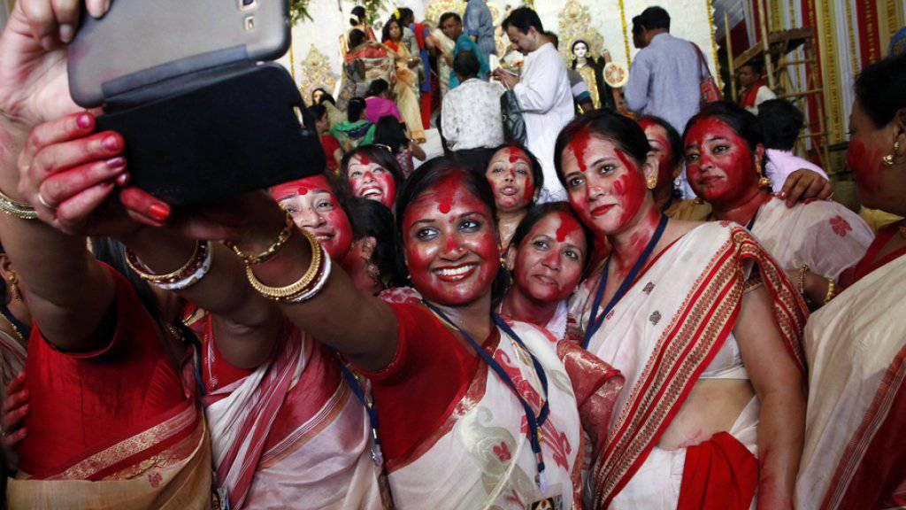 Hinduistische Frauen in Indien machen ein Selfie mit dem Handy. (Symbolbild)