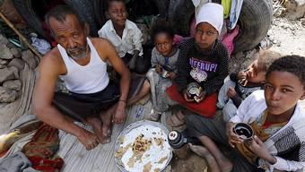 Jemenitische Bürgerkriegsopfer teilen sich eine Mahlzeit im behelfsmässigen Unterstand.