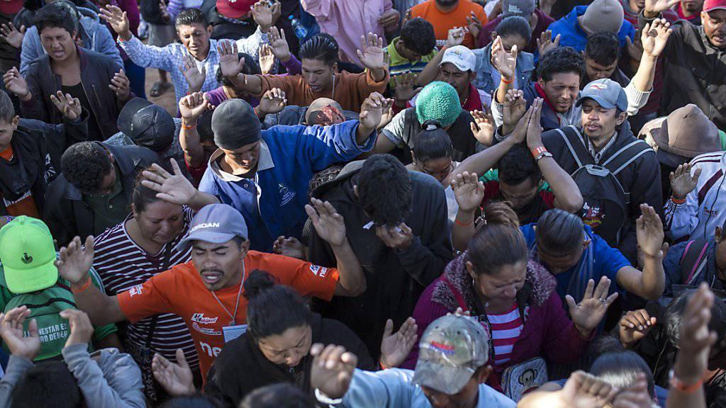 Zentralamerikanische Migranten beim Gebet in der mexikanischen Grenzstadt Tijuana: Sie hoffen auf ein besseres Leben in den USA.