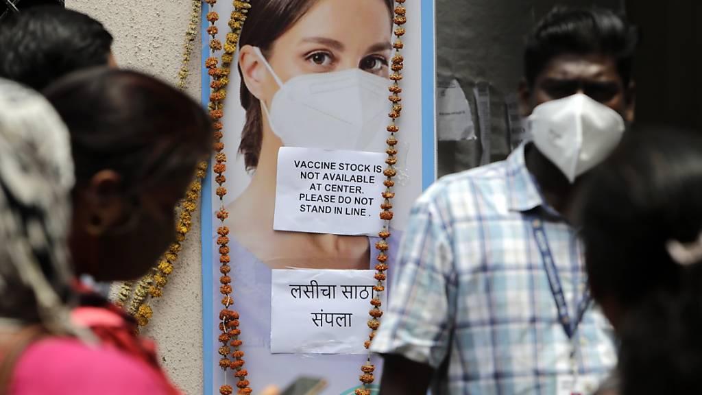 Menschen stehen vor einem Impfzentrum in Mumbai, das wegen eines Mangels an Corona-Impfstoffen geschlossen wurde. Foto: Rajanish Kakade/AP/dpa