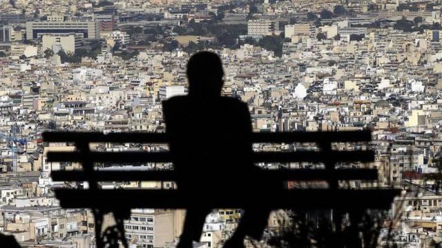 Ein Mann sitzt auf einer Bank und blickt auf die Stadt Athen