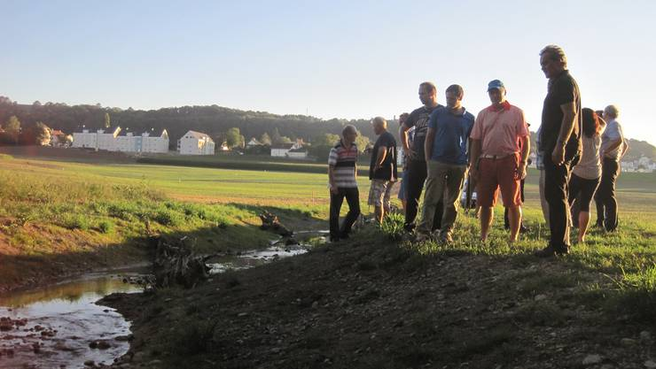 Die geladenen Gäste besichtigen den neuen Wannenmoosbachlauf vor der Einmündung in den Aabach. aka