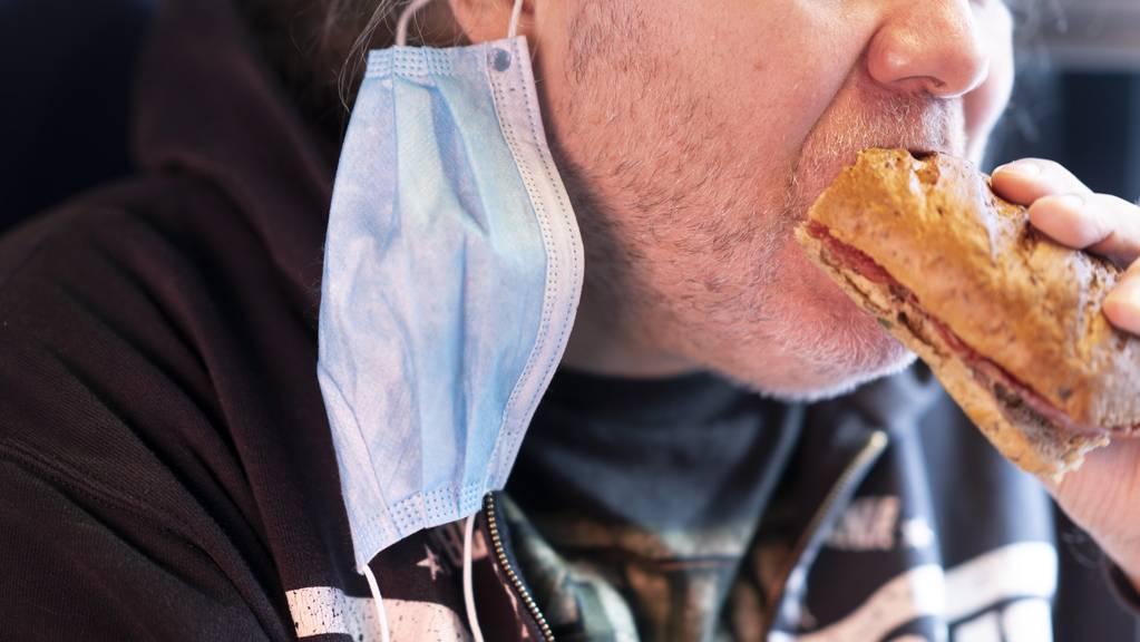 Ein Mann isst im Zug ein «Brötli». Das darf er.