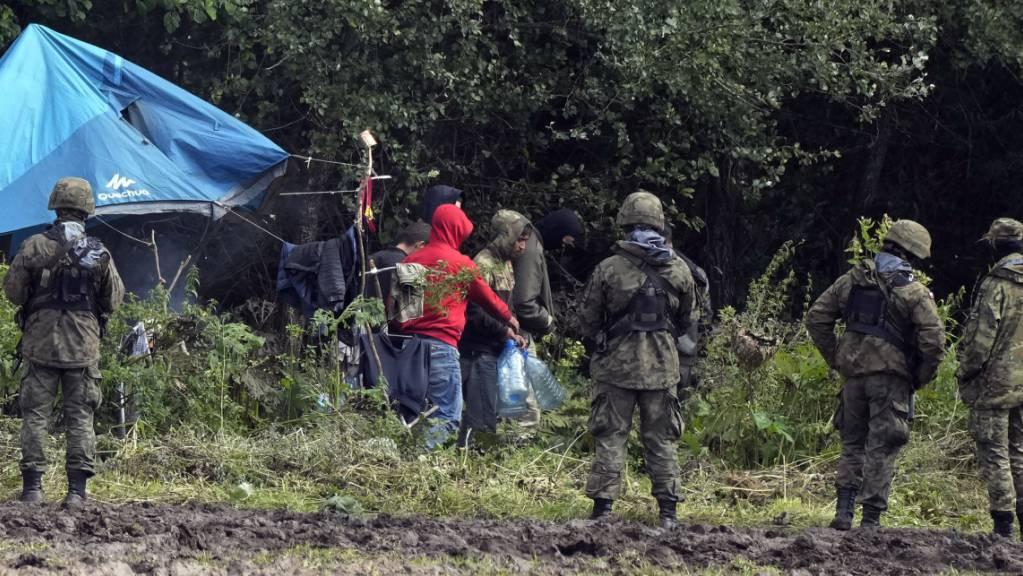 Migranten tragen Wasserflaschen, während sie an der polnisch-belarussischen Grenze in der Nähe des Ortes Usnarz Gorny im Nordwesten Polens festsitzen und von polnischen Beamten umstellt werden.