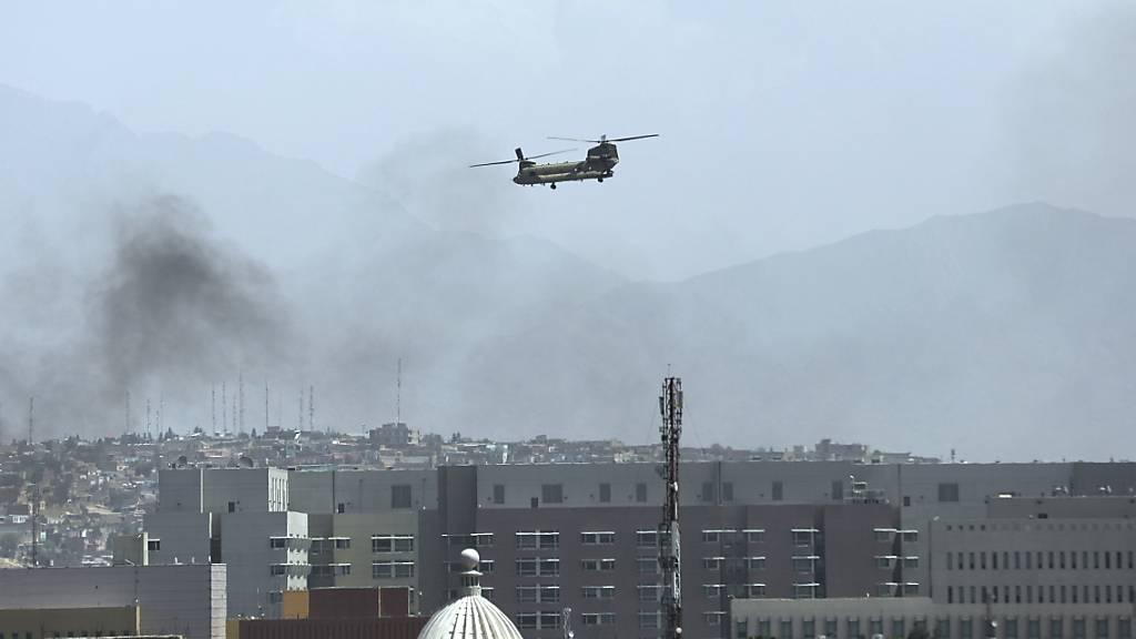 Ein Hubschrauber der USA überfliegt Kabul. Taliban-Kämpfer sind in die Außenbezirke der afghanischen Hauptstadt eingedrungen und haben das Land weiter unter ihre Kontrolle gebracht, während in Panik geratene Angestellte aus Regierungsbüros flohen und Hubschrauber bei der US-Botschaft landeten. Foto: Rahmat Gul/AP/dpa