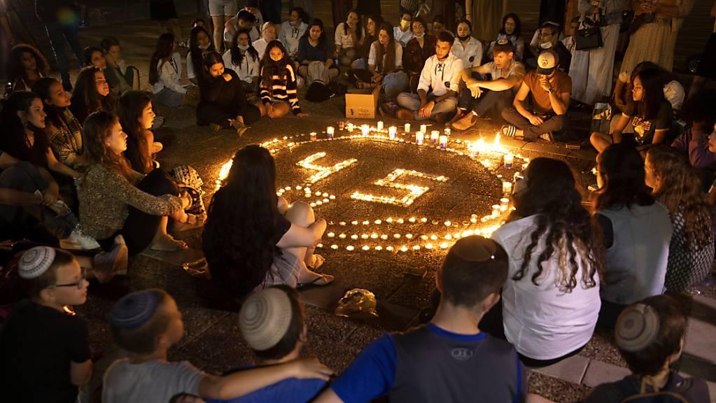 Menschen sitzen während einer Mahnwache um einen Kreis von Kerzen zum Gedenken an die 45 Opfer, die bei einer Massenpanik an einem Wallfahrtsort ums Leben gekommen sind.