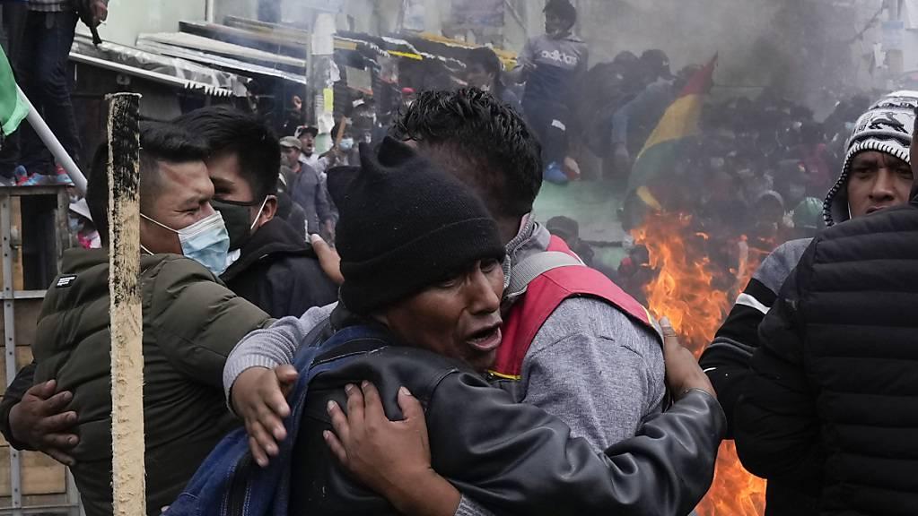 Regierungsgegnerische Koka-Bauern umarmen sich nach einem Zusammenstoß mit der Polizei in der Nähe des Kokamarktes.