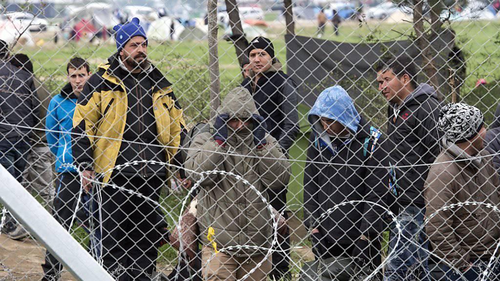 Flüchtlinge warten hinter einem Zaun an der griechisch-mazedonischen Grenze.