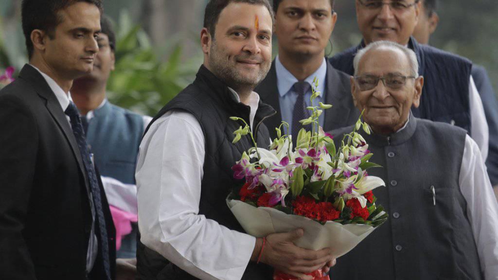 Rahul Gandhi (Mitte) mit Blumenstrauss - er führt künftig  Indiens Kongresspartei an.