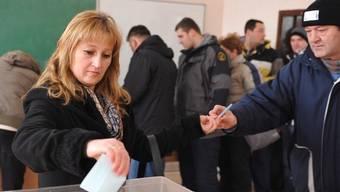 Eine Frau gibt in Mitrovica im Kosovo ihre Stimme ab
