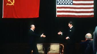 Historisch: Michail Gorbatschow, Generalsekretär der KPdSU (l), und der US-amerikanische Präsident Ronald Reagan gehen am 19. November 1985 während ihres Gipfeltreffens im Internationalen Pressezentrum in Genf mit ausgestreckten Händen aufeinander zu.