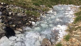 Ein Bergbach im Engadin ist über mehrere Kilometer weiss gefärbt.