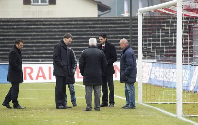 Gefroren oder nicht? Schiedsrichter und Clubverantwortliche des FCA inspizieren den Platz.