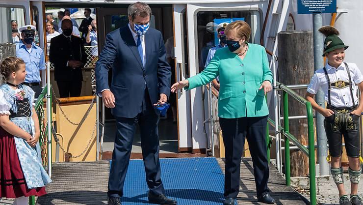 Markus Söder (CSU), Ministerpräsident von Bayern, empfängt an der Schiffsanlegestelle Prien Bundeskanzlerin Angela Merkel (CDU), um anschließend mit einem Schiff der Chiemsee-Schifffahrt auf die Insel Herrenchiemsee überzusetzen. Foto: Peter Kneffel/dpa/Pool/dpa