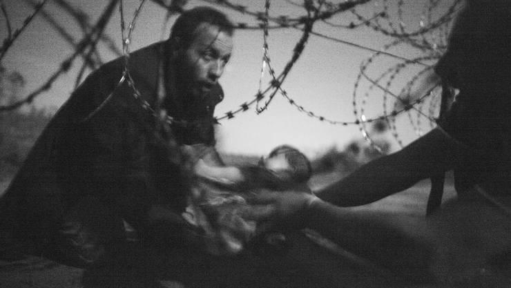 Kategorie News/Warrem Richardson (A): Ein Mann gibt sein Baby durch einen Stacheldraht-Zaun an der Grenze Serbien-Ungarn nähe Röske weiter.