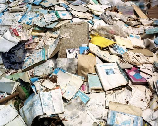 Vor einer Schule in Ishinomaki stapeln sich vermoderte Bücher.