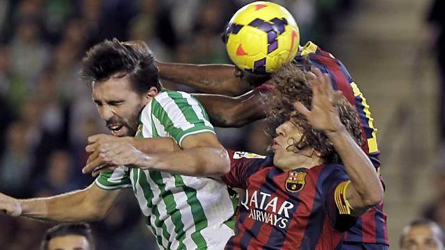 Barça-Captain Carles Puyol (m.) behauptet sich im Luftkampf.