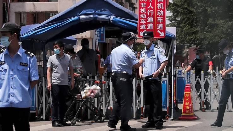 Polizeibeamte und Sicherheitsbeamte, die Schutzmasken tragen, stehen vor Wohngebäuden Wache, die nach einem positiven Fall auf einem nahe gelegenen Markt abgeriegelt wurden. Foto: Andy Wong/AP/dpa