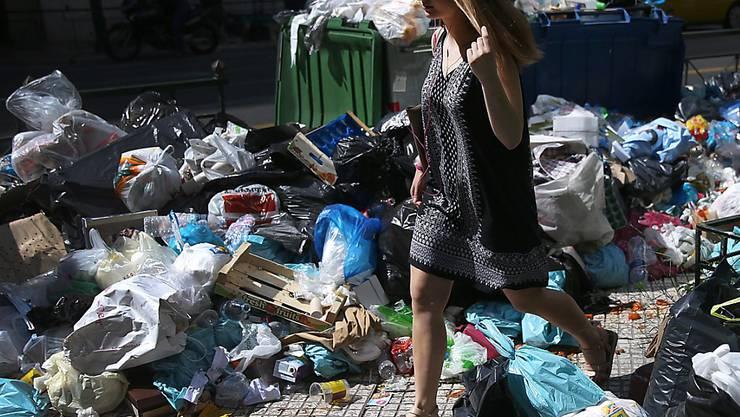 Eine Frau sucht sich in Athen den Weg durch die Abfallberge - nach fünf Tagen Streik der Müllabfuhr türmen sich die Abfälle an fast jeder Ecke der griechischen Hauptstadt.