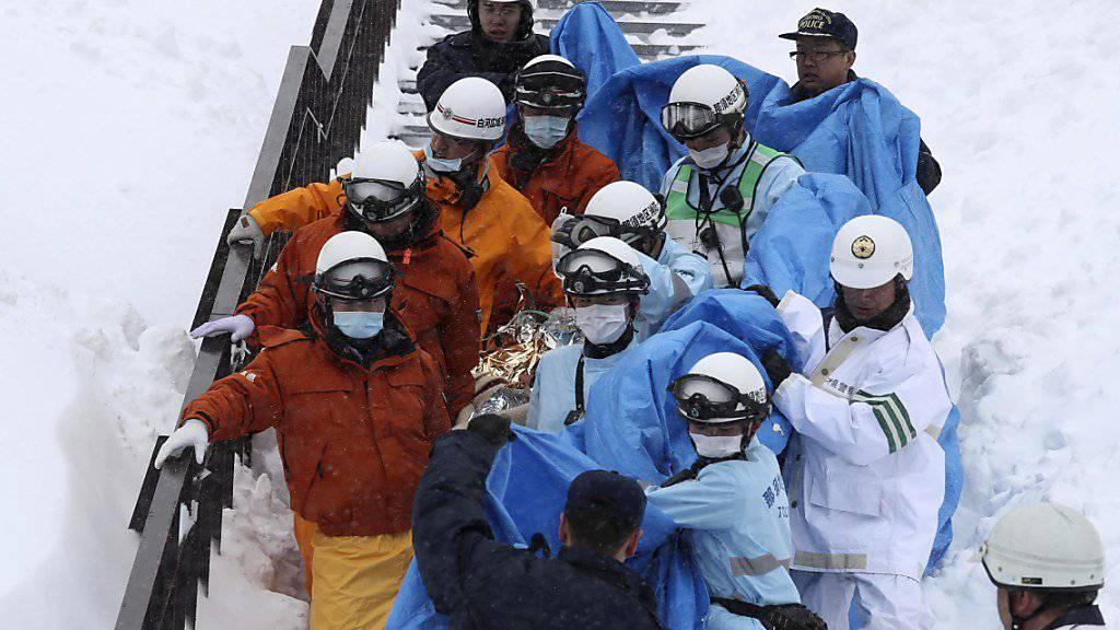 Polizisten und Rettungskräfte bergen in der Region Tochigi nach dem Lawinenabgang einen verletzten Schüler.