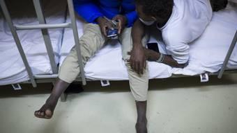 Asylsuchende vertreiben sich in einer als Unterkunft genutzten Zivilschutzanlage die Zeit am Handy. (Archivbild)