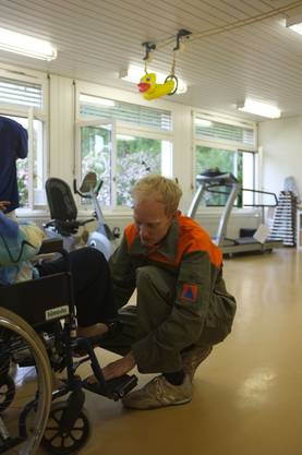 Nach der Gymnastikstunde hilft ein Zivilschützer einer Patientin und bereitet den Rollstuhl für den Weg in den Wohnbereich vor.