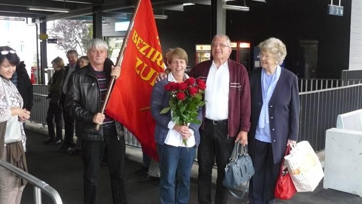 Die neue SP Grossrätin Monika Stadelmann mit roten Rosen und im Hintergrund der Bezirksfahne der SP.