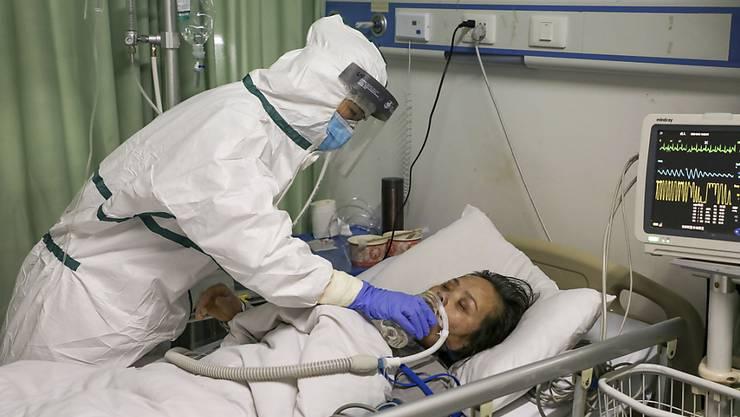 Eine Pflegefachfrau in einem Spital in der chinesischen Stadt Wuhan gibt einem am neuartigen Coronavirus erkrankten Patienten Wasser ein.