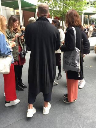 Angesagt für Männer: schwarze Plissée-Mäntel oder ganze Anzüge. Wenn möglich noch mit Rüscheli.