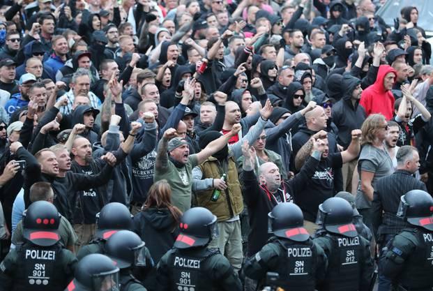 Polizisten stehen in der Innenstadt am Karl-Marx-Monument bei einer Kundgebung der rechten Szene, um ein Aufeinanderprallen von rechten und linken Gruppen zu verhindern. Nach einem Streit war in der Nacht zu Sonntag in der Innenstadt ein 35-jaehriger Mann erstochen worden. Die Tat war Anlass für spontane Demonstrationen, bei denen es auch zu Jagdszenen und Gewaltausbruechen kam.