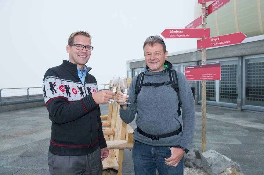 Andreas Marty und Lorenz Thöni stossen auf das neue Bänkli und ihre Partnerschaft an. (Bild: Edelweiss/Fabienne Bühler)