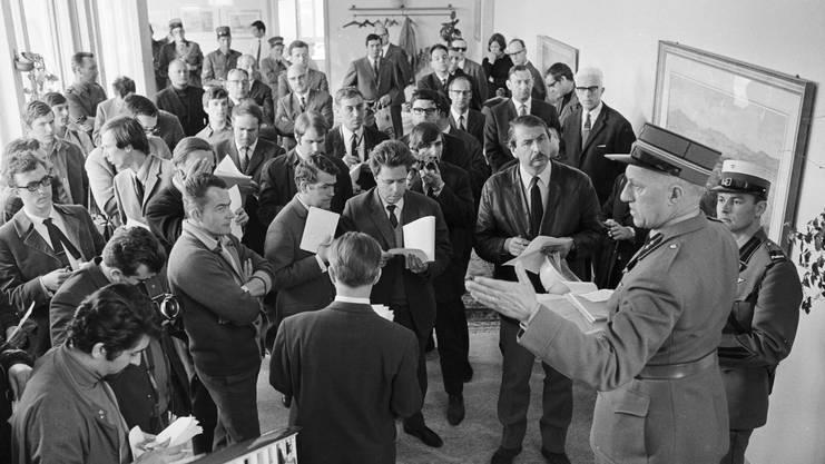 Stehend verfolgen die über 40 Journalisten aus der ganzen Schweiz an der Pressekonferenz die Ausführungen von Oberleutnant Fritz Meier.