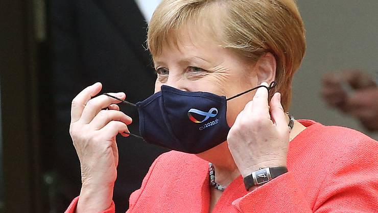 dpatopbilder - Bundeskanzlerin Angela Merkel (CDU) nimmt im Bundesrat ihre Mund- und Nasenschutzmaske ab, bevor sie eine Rede zu Zielen der EU-Ratspräsidentschaft hält. Foto: Wolfgang Kumm/dpa
