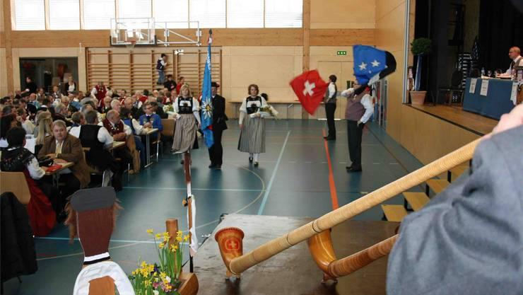 Die Vereinsfahne, begleitet von Cécile Loosli und Nina Traber, wird von René Beguelin unter Alphornklängen feierlich präsentiert.