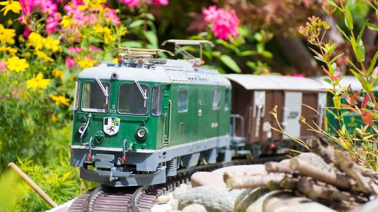 Ein Güterzug der Rhätischen Bahn vom Modellbahnhersteller LGB durchfährt den Garten von Stefan Wyss.