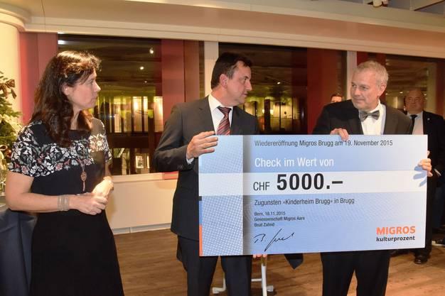 Rolf von Moos, Gesamtleiter Kinderheim Brugg (rechts), erhält den Check von Matthias Wolf , Migros Marktleiter Brugg, sowie Andrea Bauer, Mediensprecherin Migros Aare