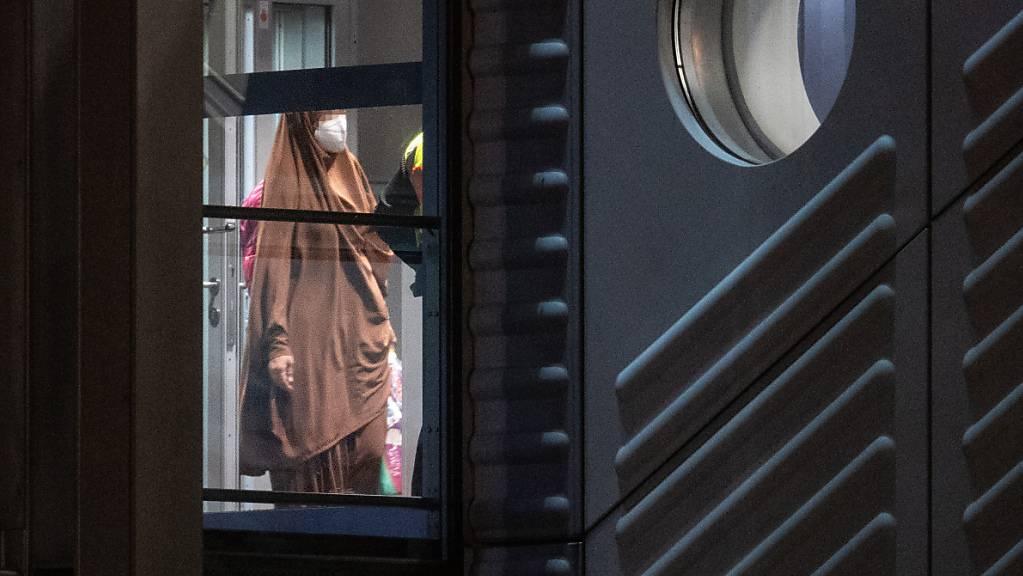 Eine verschleierte Frau mit einer Maske betritt aus der Gangway einer Chartermaschine heraus einen abgeschirmten Bereich der Bundespolizei am Flughafen Frankfurt. Foto: Boris Roessler/dpa