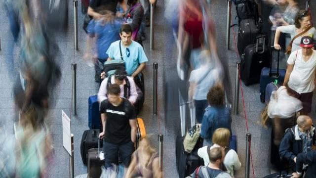 Reisende warten an einem Check-In-Schalter am Flughafen Zürich