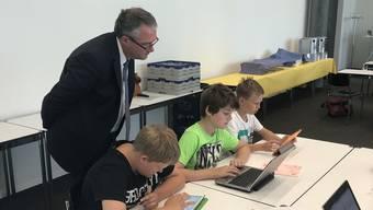 Regierungsrat Remo Ankli schaut Primarschülern aus Effingen über die Schulter, die mit Mindsteps üben. Das können sie auch zu Hause am PC, Laptop oder Tablet.