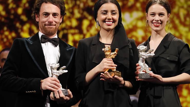 Die Tochter des iranischen Preisträger-Regisseurs, Baran Rassulof (Mitte), nimmt in Berlin den Goldenen Bären für ihren Vater in Empfang, der nicht ausreisen durfte. Umrahmt wird sie von der besten Darstellerin Paula Beer (rechts) und dem besten Darsteller Elio Germano.