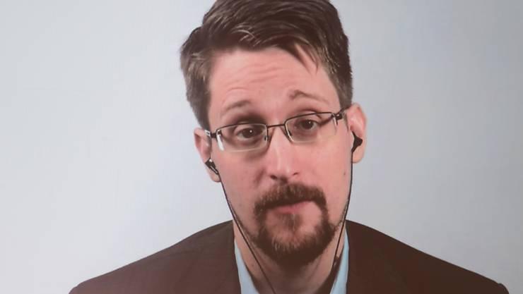 ARCHIV - Edward Snowden ist auf einer Video-Leinwand in der Urania zu sehen, während er bei einer Liveübertragung über sein Buch «Permanent Record: Meine Geschichte» spricht. Foto: Jörg Carstensen/dpa
