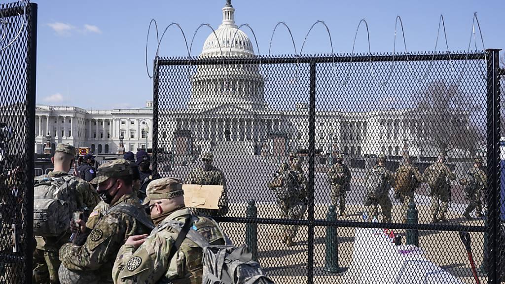 Soldaten der Nationalgarde gehen durch das Tor eines Sicherheitszauns vor dem Kapitol. Foto: Jacquelyn Martin/AP/dpa