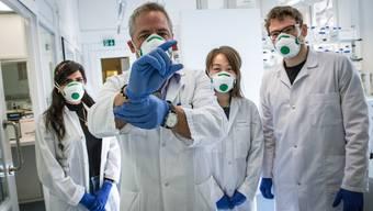 Martin Bachmann mit Teilen seines Teams im Inselspital Bern. Im Röhrchen ist eine erste Version seines Impfstoffs.