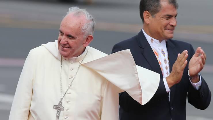 Papst Franziskus (l) wurde nach seiner Ankunft in Ecuador bei windigem Wetter von Präsident Rafael Correa empfangen.
