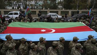 Aserbaidschanische Soldaten tragen eine große Fahne in den Farben ihrer Nationalflagge, während sie die Rückgabe der Region Latschin feiern. Foto: Emrah Gurel/AP/dpa