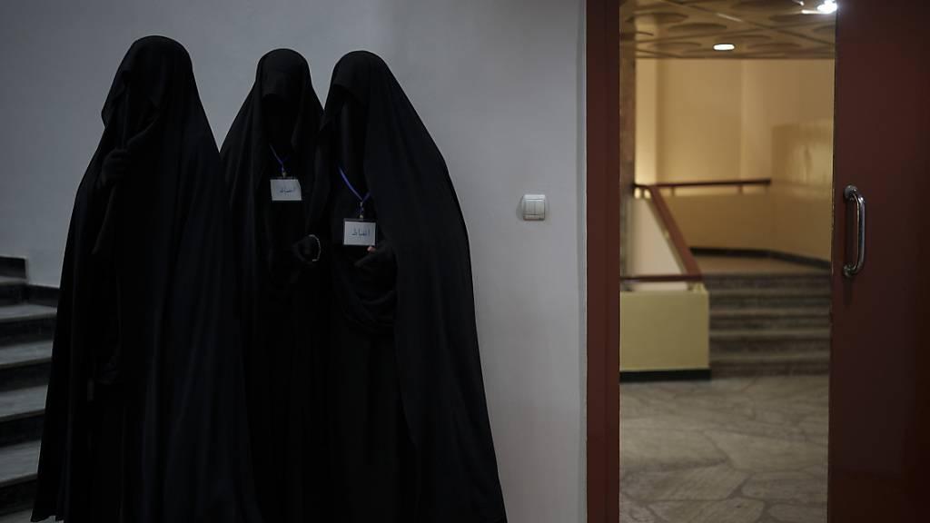 Drei in schwarzen Burkas gehüllte Frauen stehen vor einem Hörsaal der Universität in Kabul. Bei einer Demonstration zogen dutzende Frauen über das Gelände der Universität, wo sie ihre Unterstützung für die Regierung der militant-islamistischen Taliban vermittelten. Foto: Felipe Dana/AP/dpa