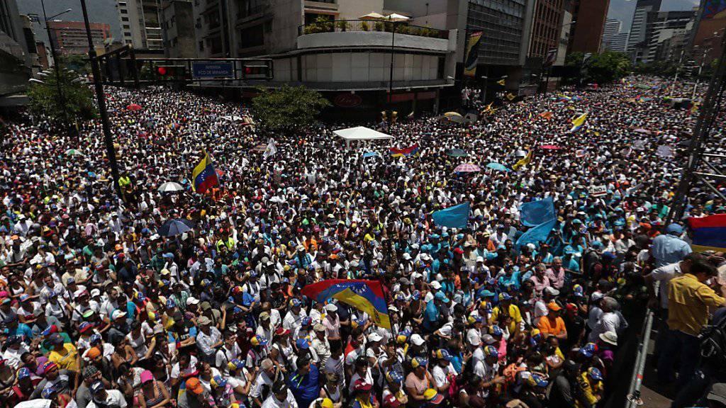 Anhänger der Opposition in Venezuelas Hauptstadt Caracas marschieren auf gegen die Maduro-Regierung.
