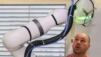 Roboter CARLO, bestaunt von Cyrill Bätscher vom Entwicklungsteam.