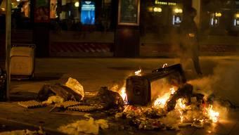 Ein Müllcontainer brennt in Madrid während eines Protests gegen die Ausgangssperre. Spanien ist eines der von der Corona-Krise am schwersten getroffenen Länder Westeuropas. Foto: Manu Fernandez/AP/dpa